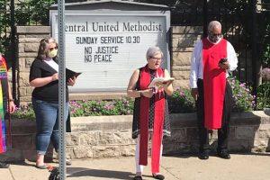 Rev Jill Zundell reading in front of Central United Methodist church in Detroit
